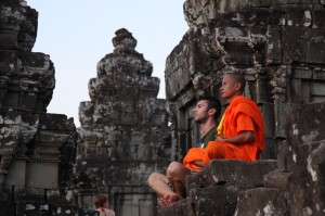 A monk teaching a westerner to meditate at Phnom Bakheng